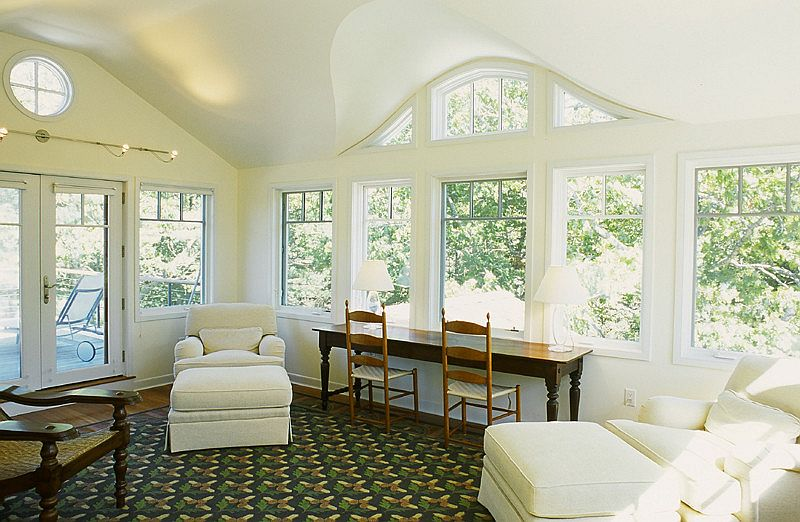 Cozy seating and a work desk add to the appeal of the sunroom [Design: Beckstrom Architecture/Planning + Consulting]