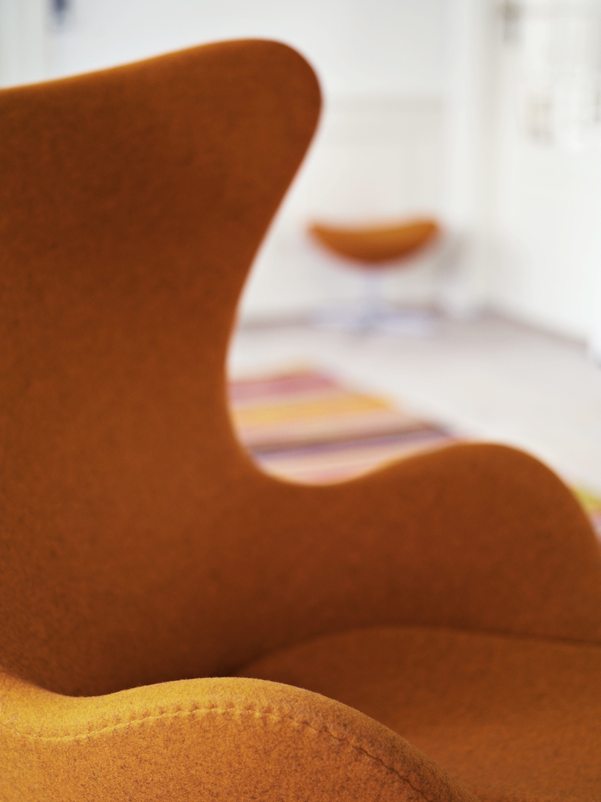 The Egg™ chair's iconic profile. Upholstered with orange Divina Melange fabric.