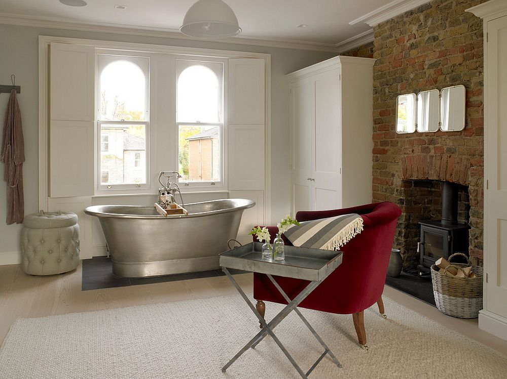 Fireplace and a bright red armchair along with side table transform the transitional bathroom