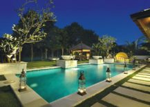 Gorgeous tropical pool with lantern lighting and a gazebo in the distance