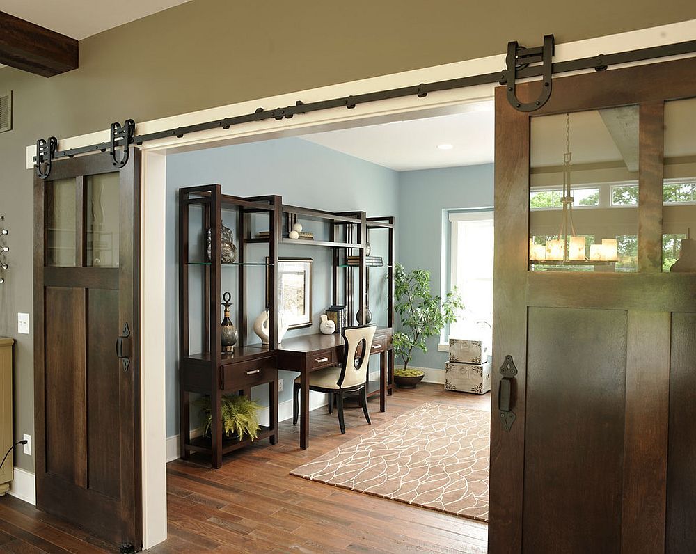 Industrial, barn-style doors conceal a spacious and traditional home office