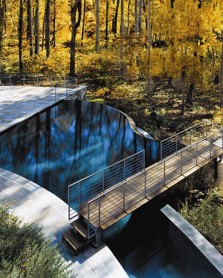Free-form, contemporary pool with a bridge above it that leads into the woods [From: Lewis Aquatech - Julia Heine/McInturff Architects]