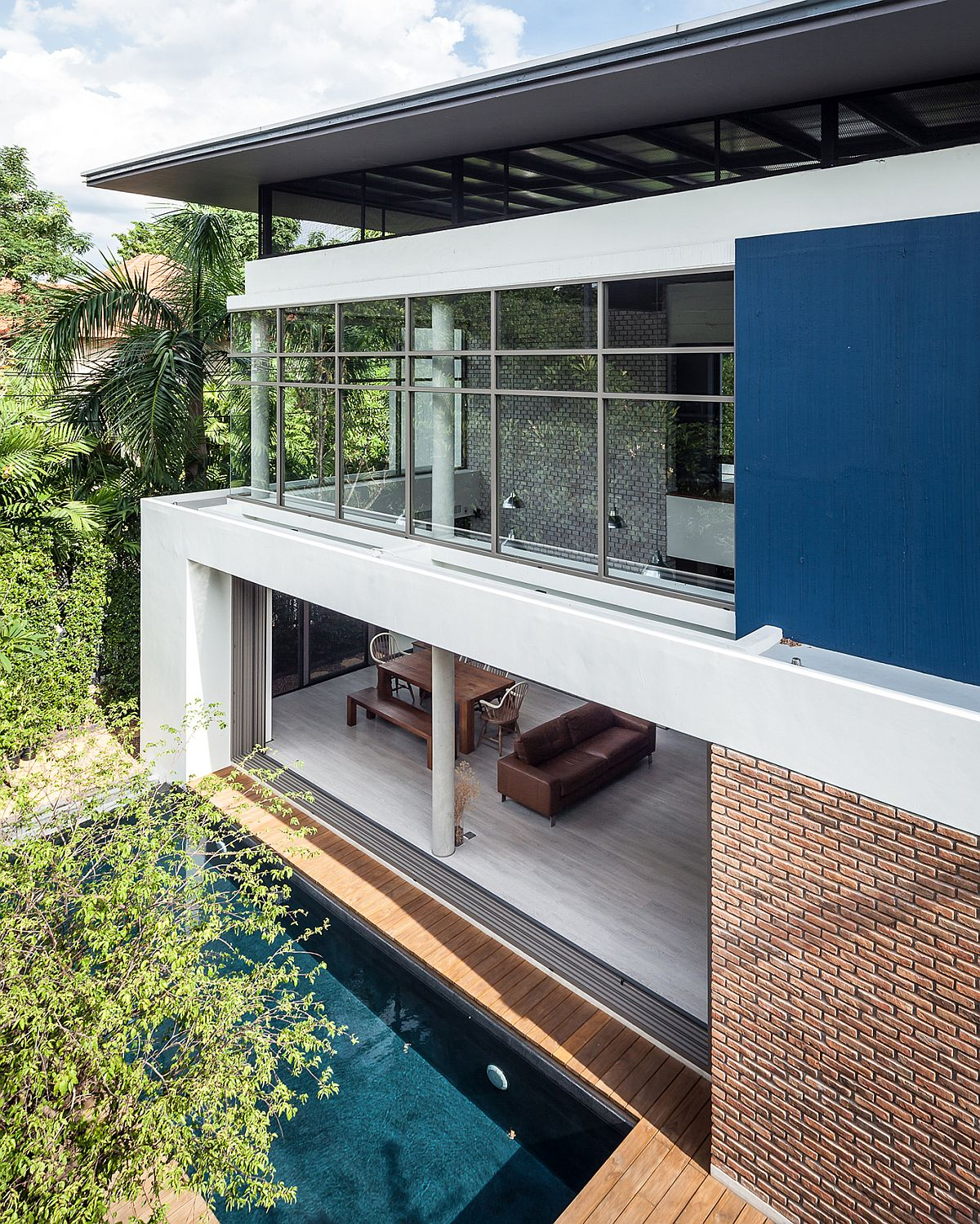 Large sliding glass doors and windows open up the Thai home towards the patio and pool area