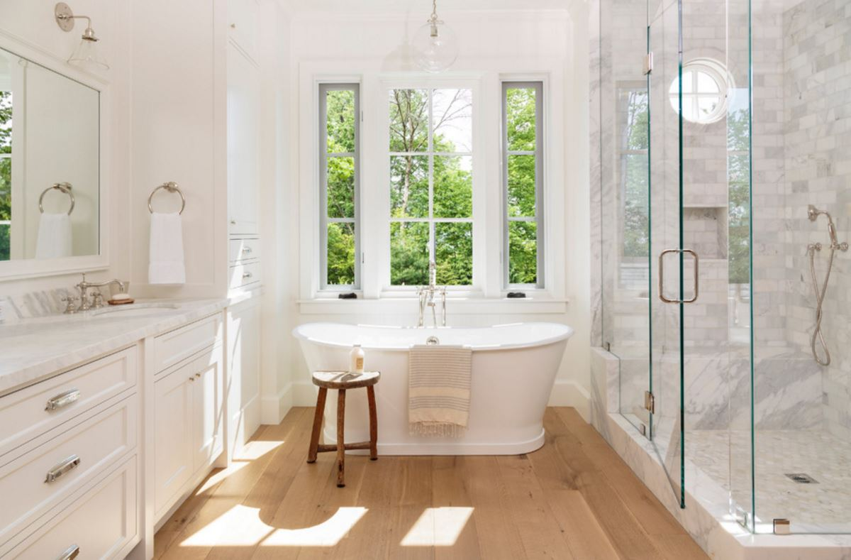 Light-filled bathroom with a wooden stool