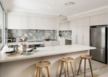 Lovely patchwork tiled backsplash in the kitchen adds color to the Scandinavian setting