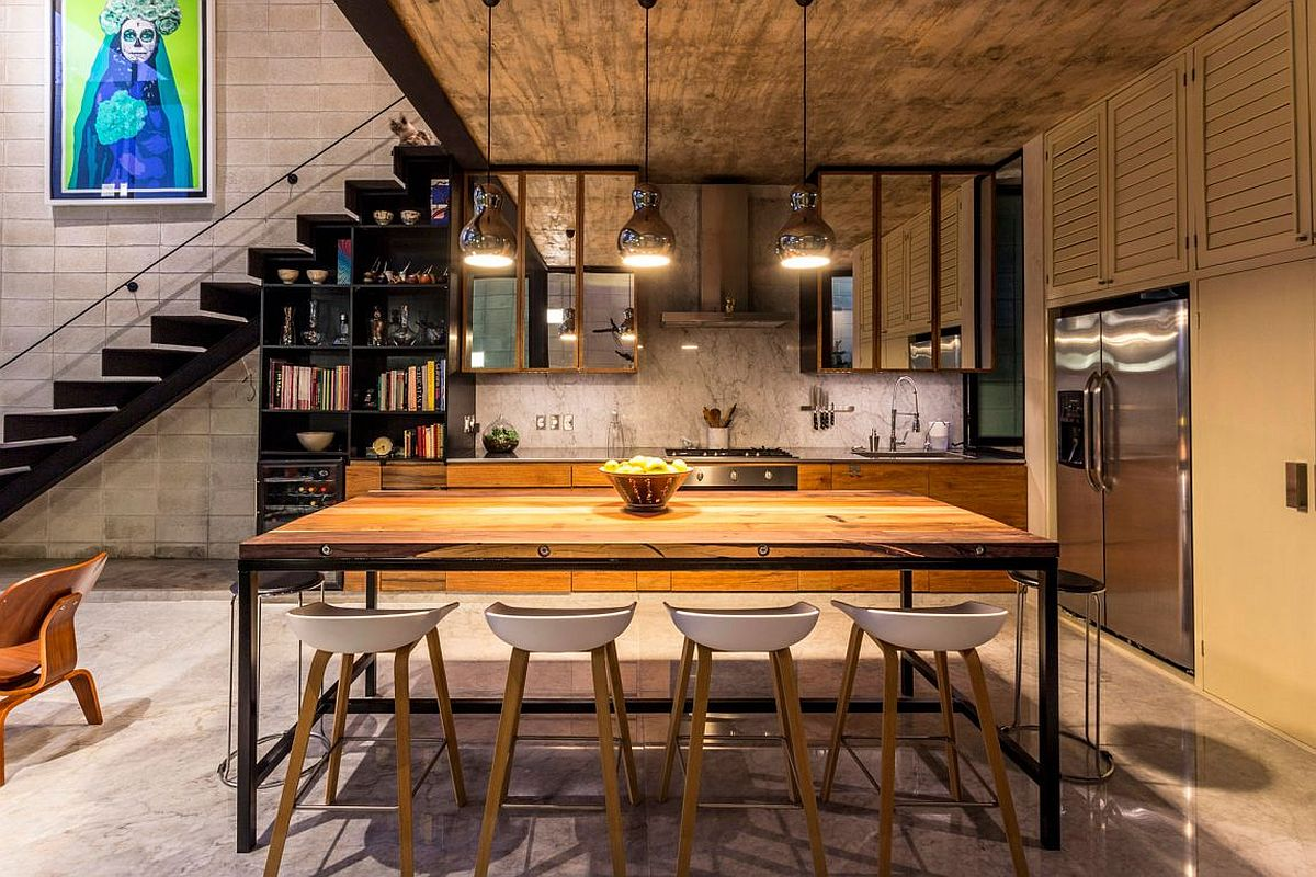 Metallic pendant lights for the dining space with a bookshelf and kitchen in the backdrop