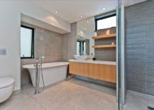 Modern bathroom with floating vanity, white bathtub and floating shelves