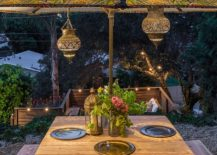 Moroccan lanterns and patterned umbrella complete an eclectic outdoor dining space