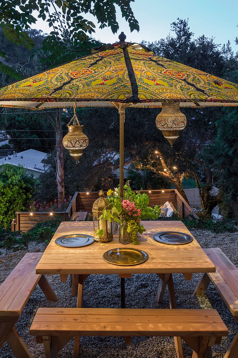 Moroccan lanterns and patterned umbrella complete an eclectic outdoor dining space [Design: Shannon Ggem / Photography: michael Kelley]
