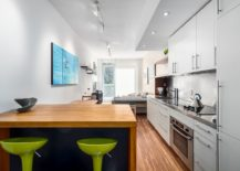 Narrow kitchen with lovely little breakfast zone and colorful bar stools