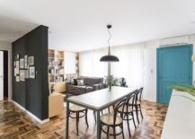 Open-living-area-of-the-small-Brazilian-apartment-with-dining-room-and-a-colorful-door-in-the-backdrop-217x155