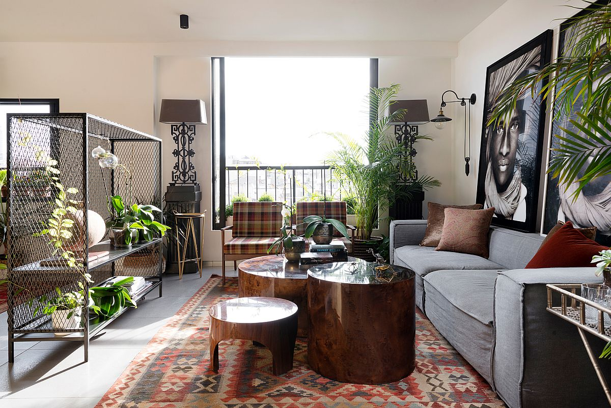 Plush gray couch, metal mesh plant holder, custom upholstered chairs and cool coffe tables shape a lovely living room