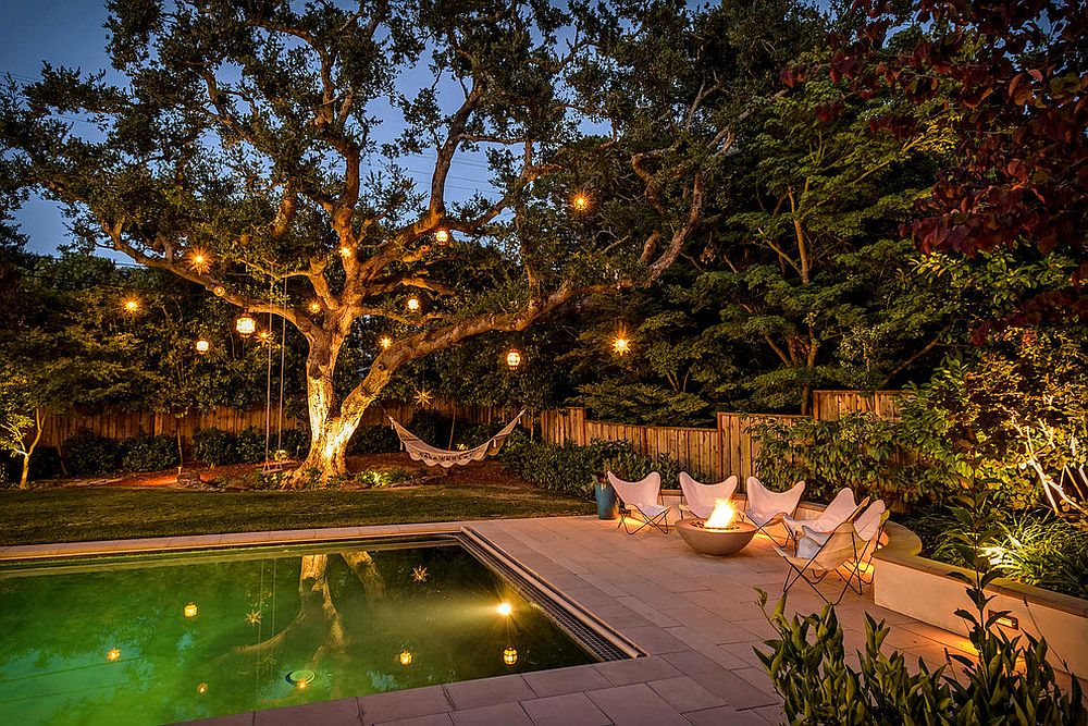 Poolside chairs, hammock and lanterns on trees for a mesmerizing backyard retreat! [From: Black Bear Builders]