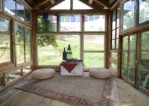 Reclaimed wood and glass shape rustic meditation shed surrounded by greenery