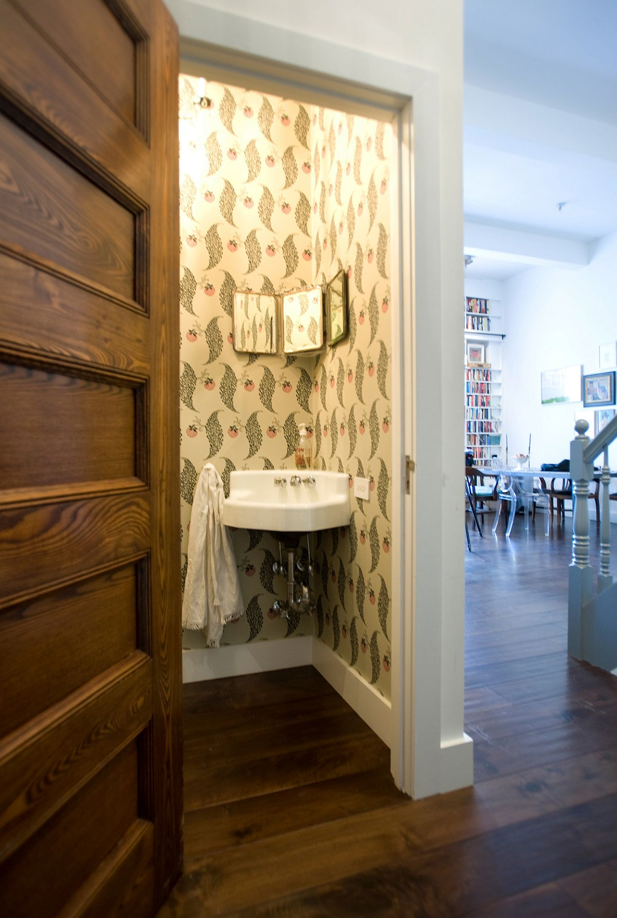 Salvaged door and vintage wallpaper revitalize the small powder room