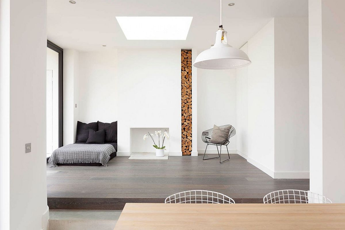 Stacked firewood is used as a decorative element inside the modern minimal London home