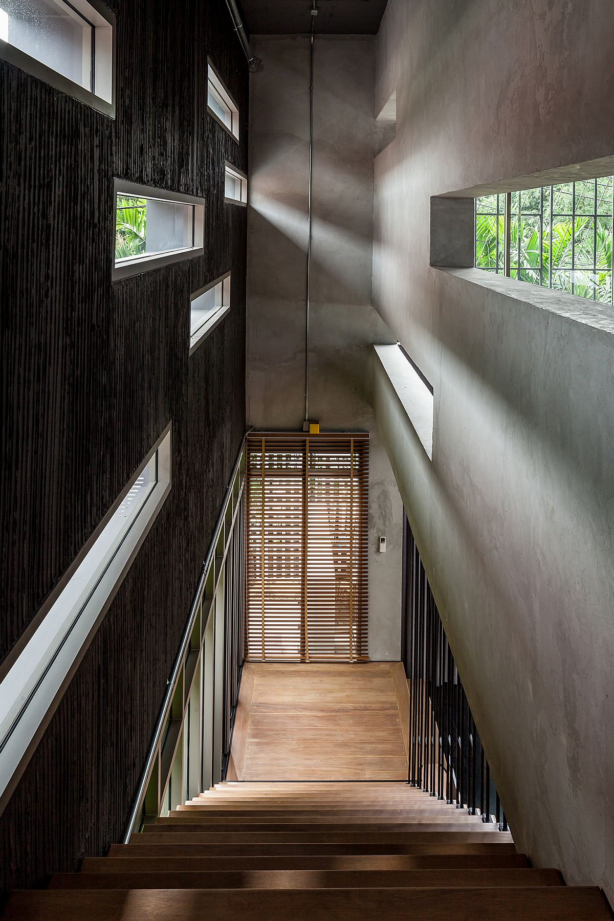 Staircase flanked by texturally two different walls fetaures little windows that bring in natural light