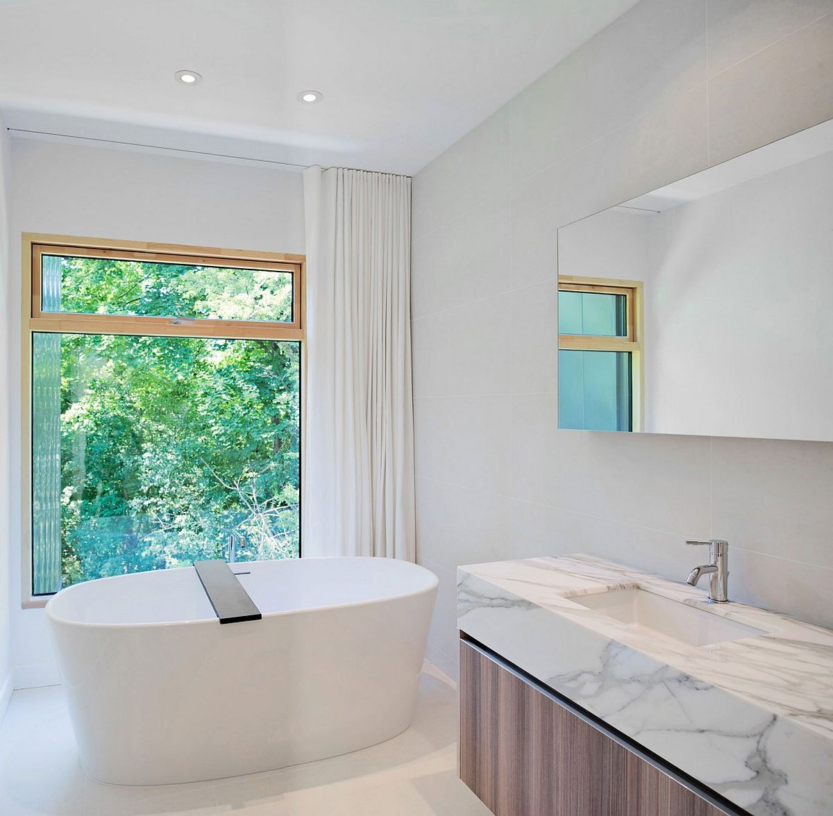 Standalone bathtub and vanity with wooden base and marble top inside the contemporary bathroom