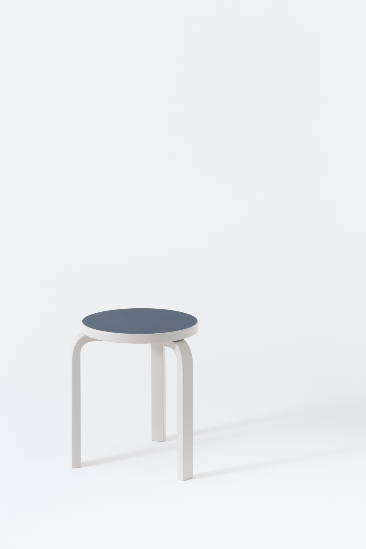 Stool 60 in stone and white lacquer. The L-leg is a solid wood leg with a laminated bend at 90°. Patented in 1933, it would become a standard featureof Alvar Aalto's furniture designs.Photo bySchaepman & Habets.