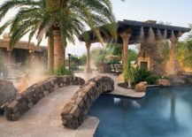 Stunning Mediterranean poolscape with stone siding that replicates natural stone