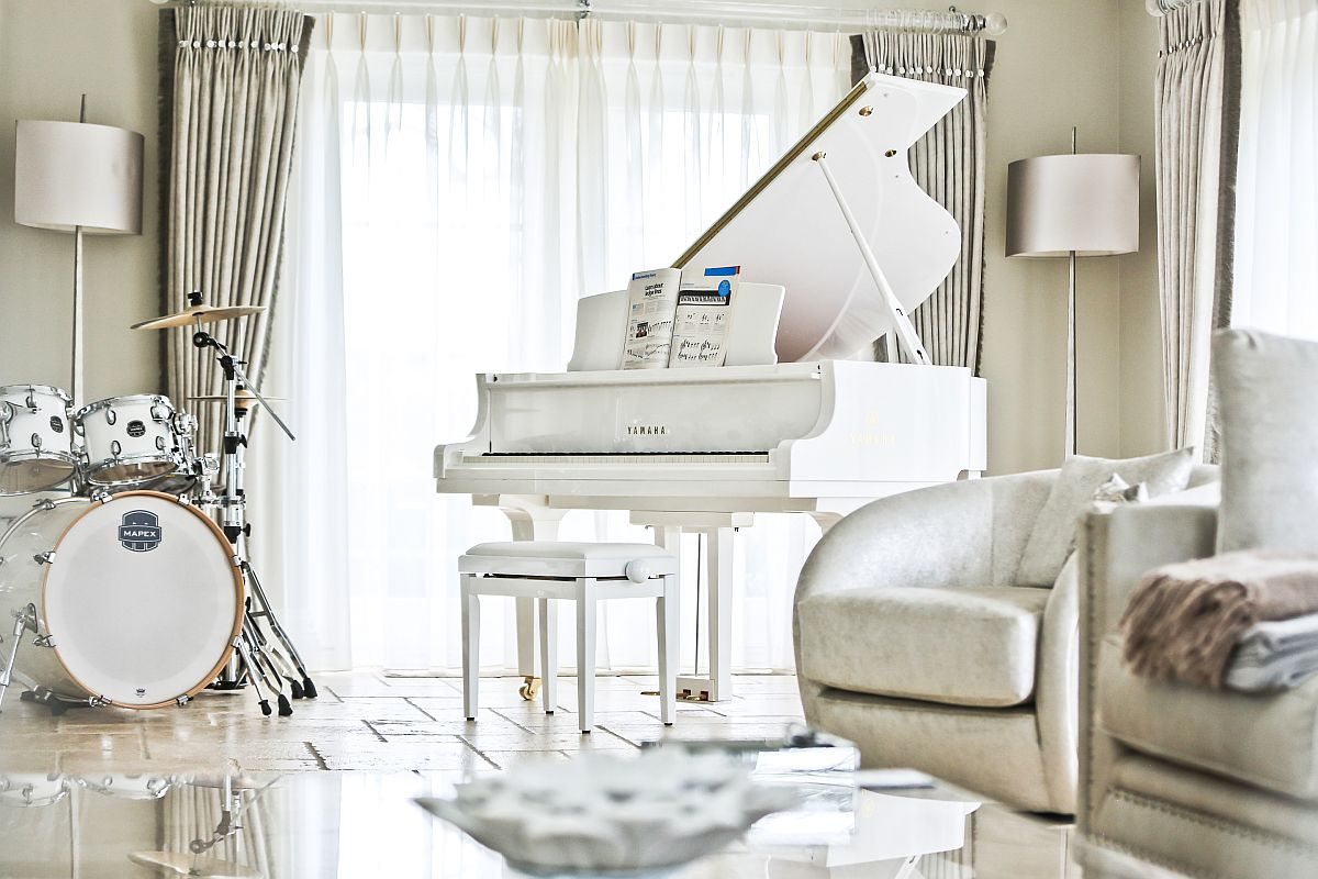 Stunning room in white with piano and drum set in matching color