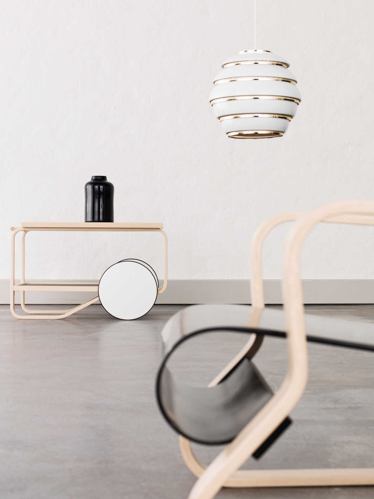 """Clockwise from left: Tea Trolley 901 (1936),Pendant Light A331 (1953) and Armchair 41 """"Paimio"""". ThePaimiolounge chair was designed in 1932 for thethe Paimio Sanatorium in Finland. Photo byOsma Harvilahti."""