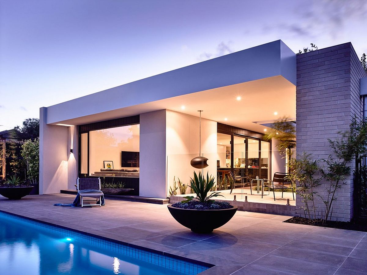 Warm indoor illumination and lovely landscape lighting combine to create a fabulous outdoor hangout