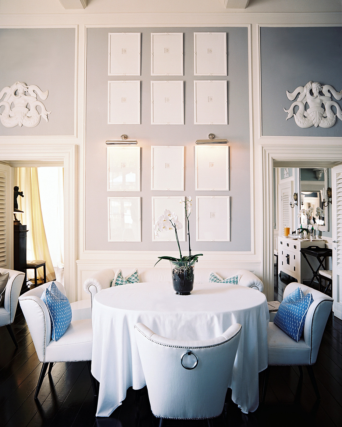 White seating surrounds a white round tablecloth