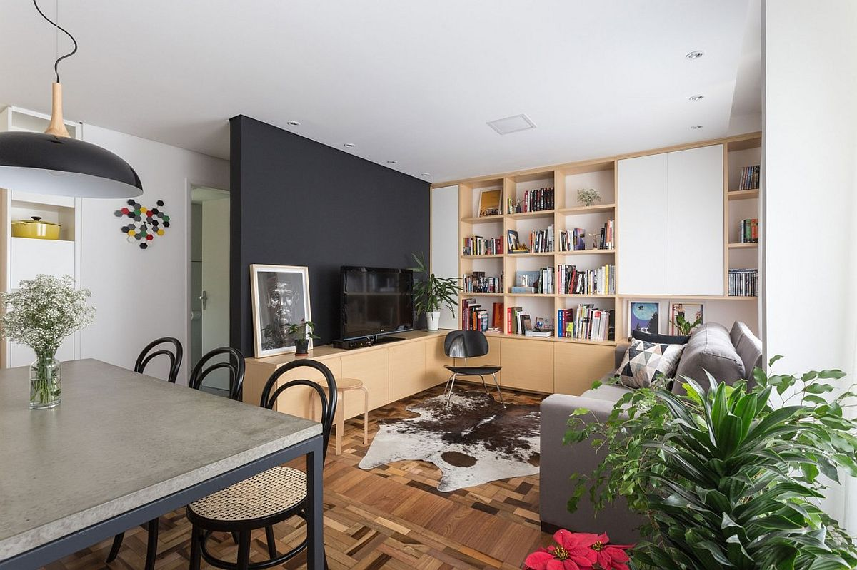 Wooden cabinets, open shelves and a black wall fashion a fabulous living area