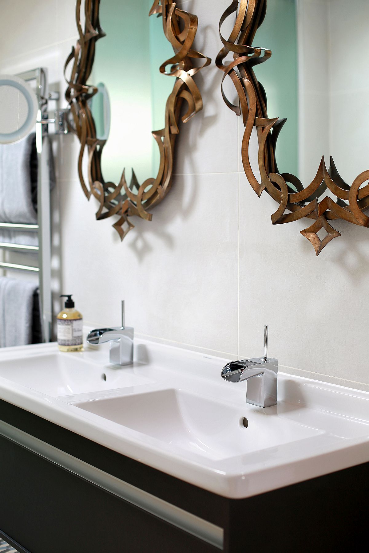 A closer look at the floating bathroom vanity and bronze mirrors