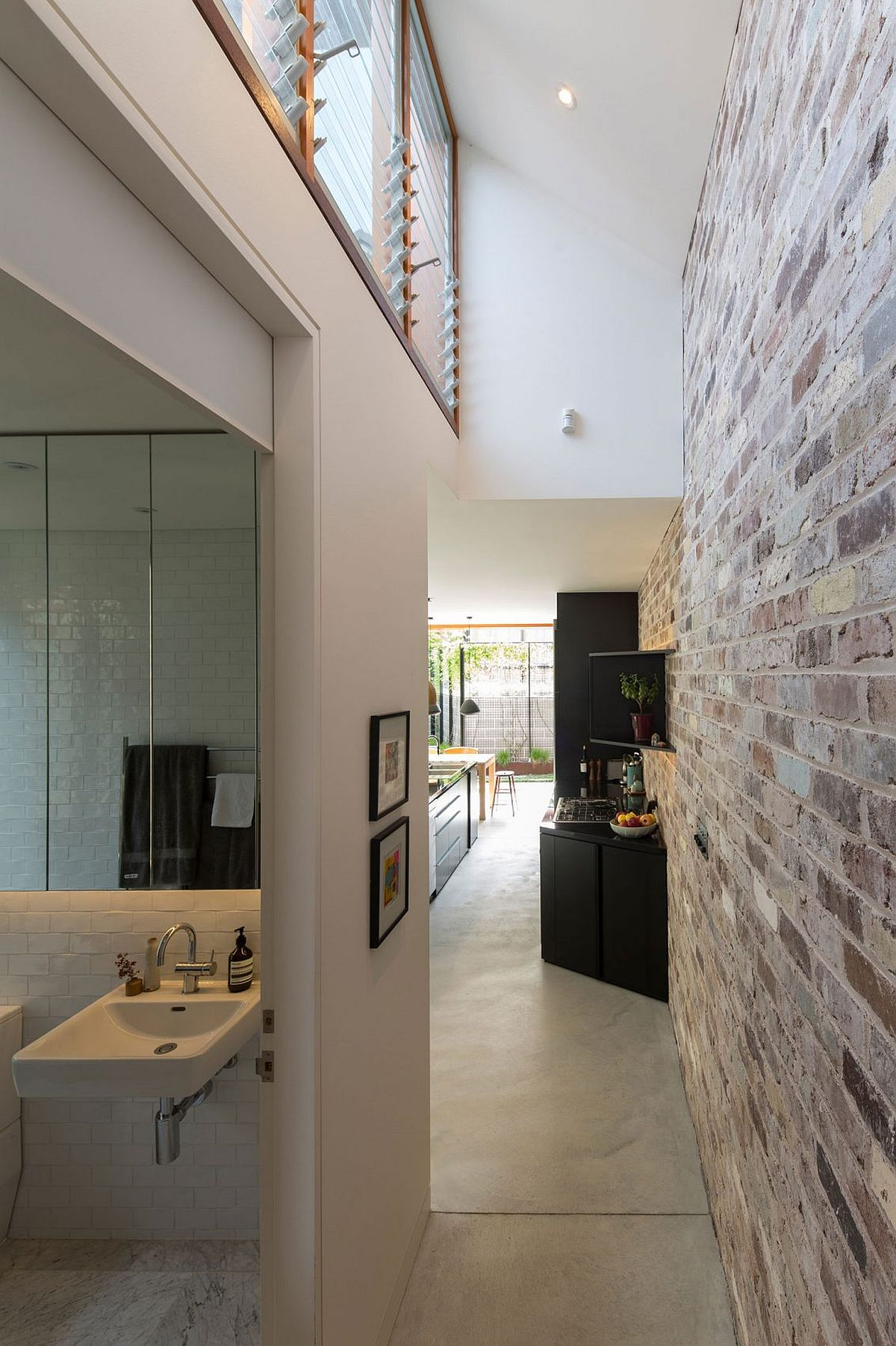 Artificial lighting coupled with natural light highlights the beauty of the exposed brick wall