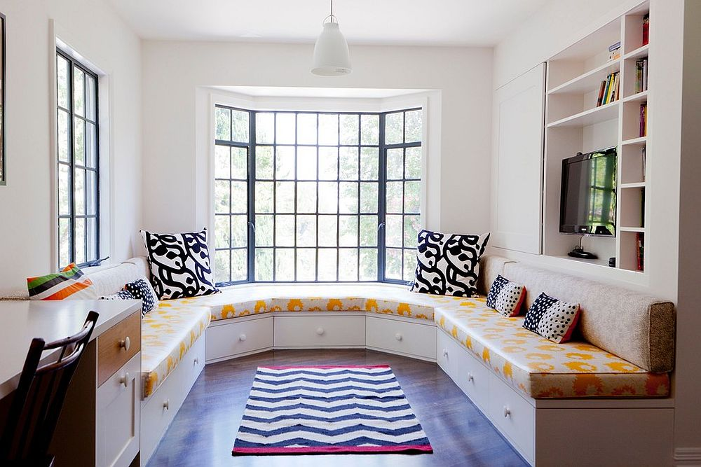 Banquette in the family room couples ample seating space with hidden storage [Design: Amy Sklar Design]