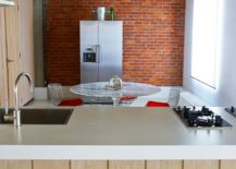 Brick wall in the backdrop of kitchen and dining room with Saarinen Tulip table