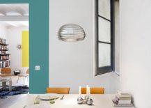 Bright, metallic pendant and window enliven the small dining space