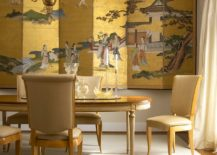 Chinese decorative screen in gold creates a dramatic backdrop for the dining room in gold