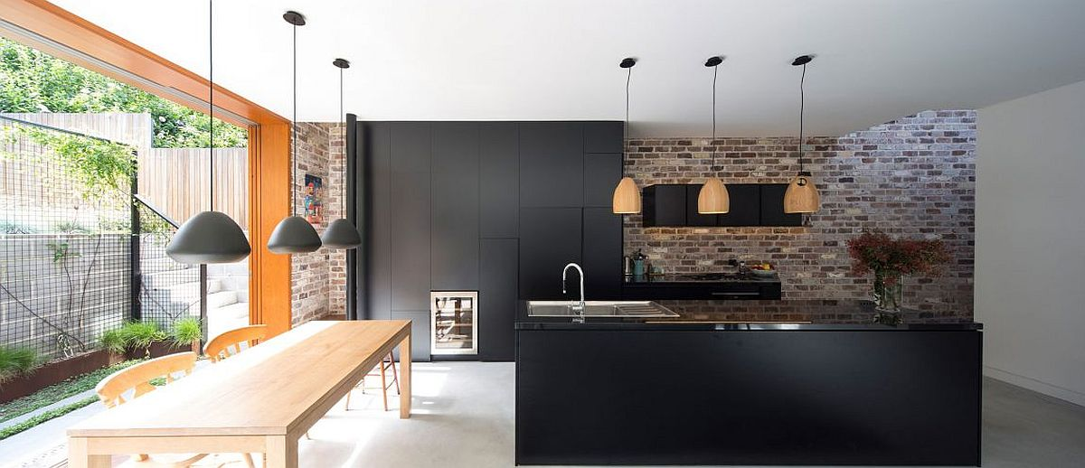 Dark kitchen cabinets and contemporary island sit next to the exposed brick wall