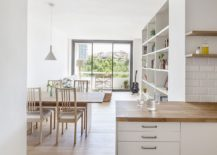 Dining area and kitchen in white with wooden accents