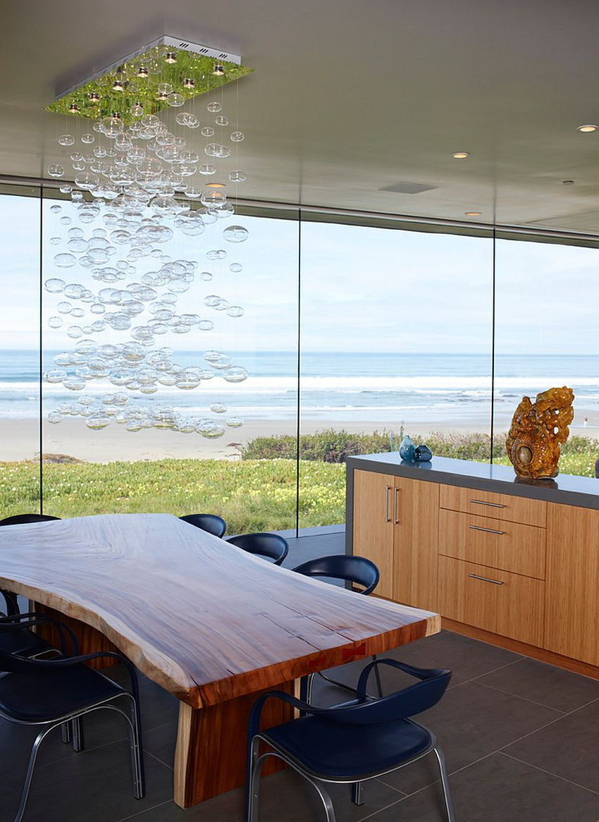 Dining room with an ocean view, cascading chandelier and a live edge dining table [Design: One World Home Furnishings]