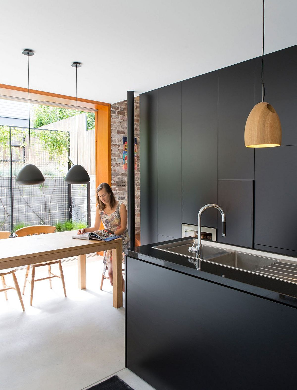 Dining space, kitchen and reading nook at the stylish Sydney home