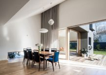 Dining space with Nelson pendants, bright blue chairs and an access to the yard