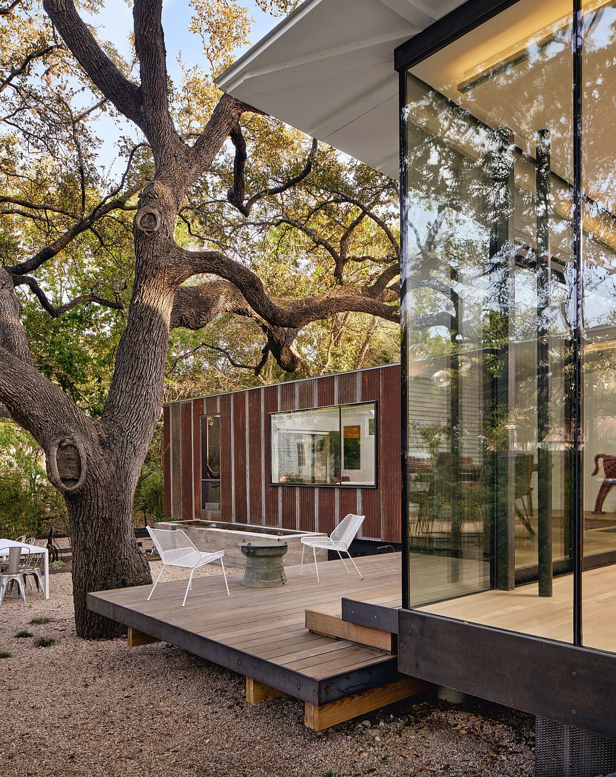 Glass walls connect the cottage with the outdoor terrace and green surroudings