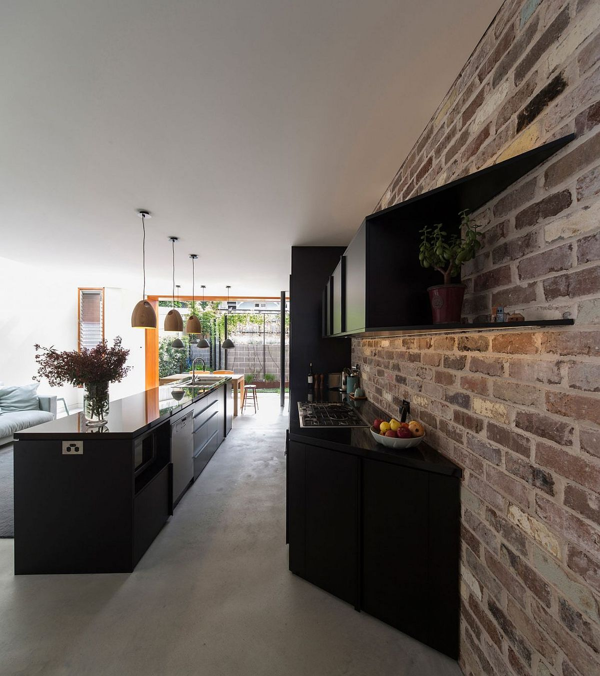 Glossy black kitchen cabinets coupled with exposed brick wall to create textural beauty