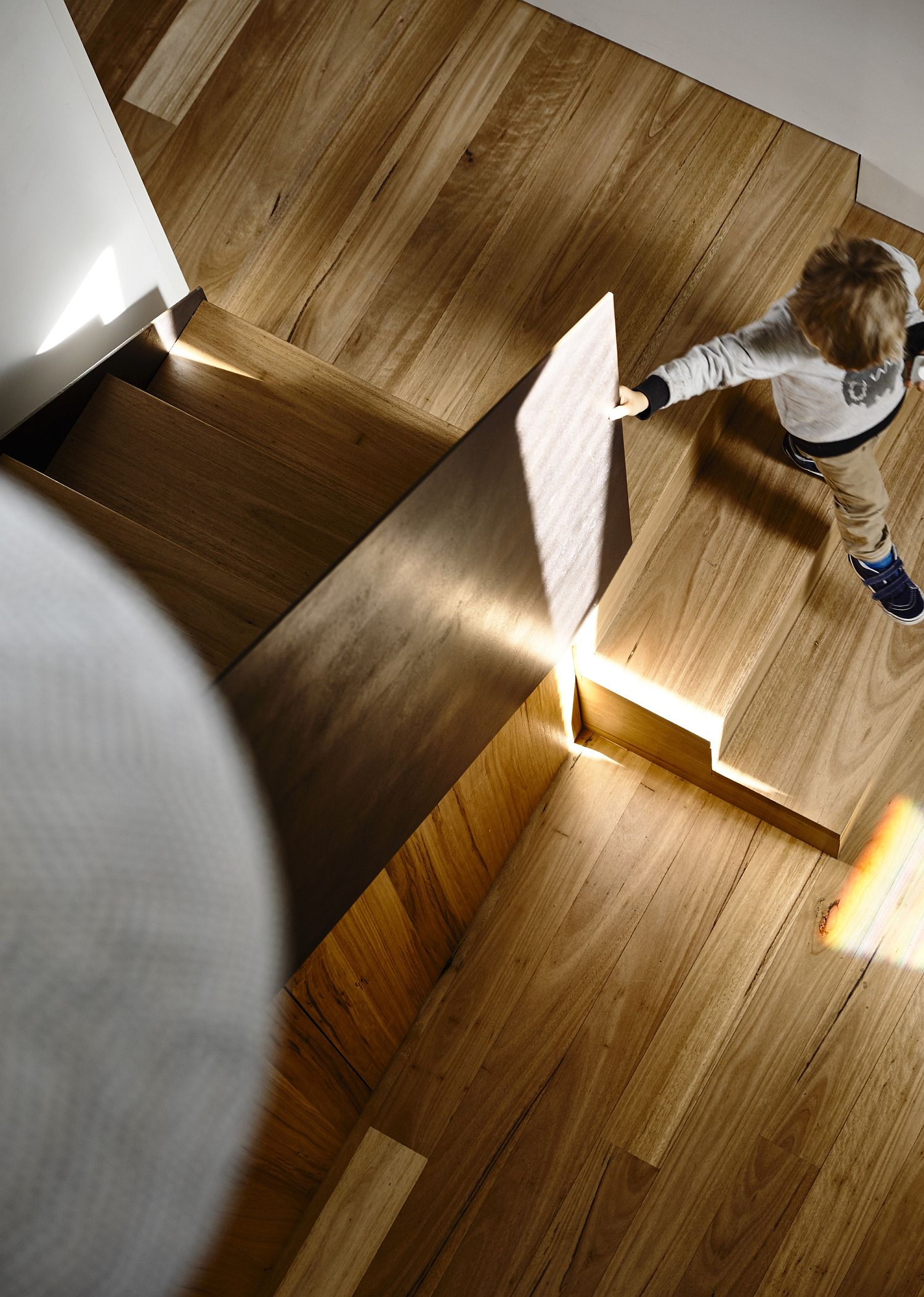 Illuminate wooden staircase leading to the bedroom level