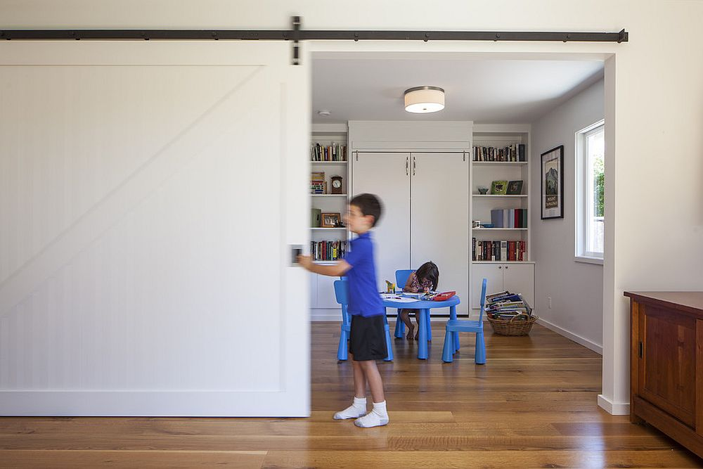 Kids' study area and playroom delineated from the rest of the home using sliding barn door [Design: Feldman Architecture]