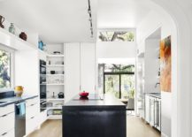 Kitchen in white with dark central island and colorful wall art
