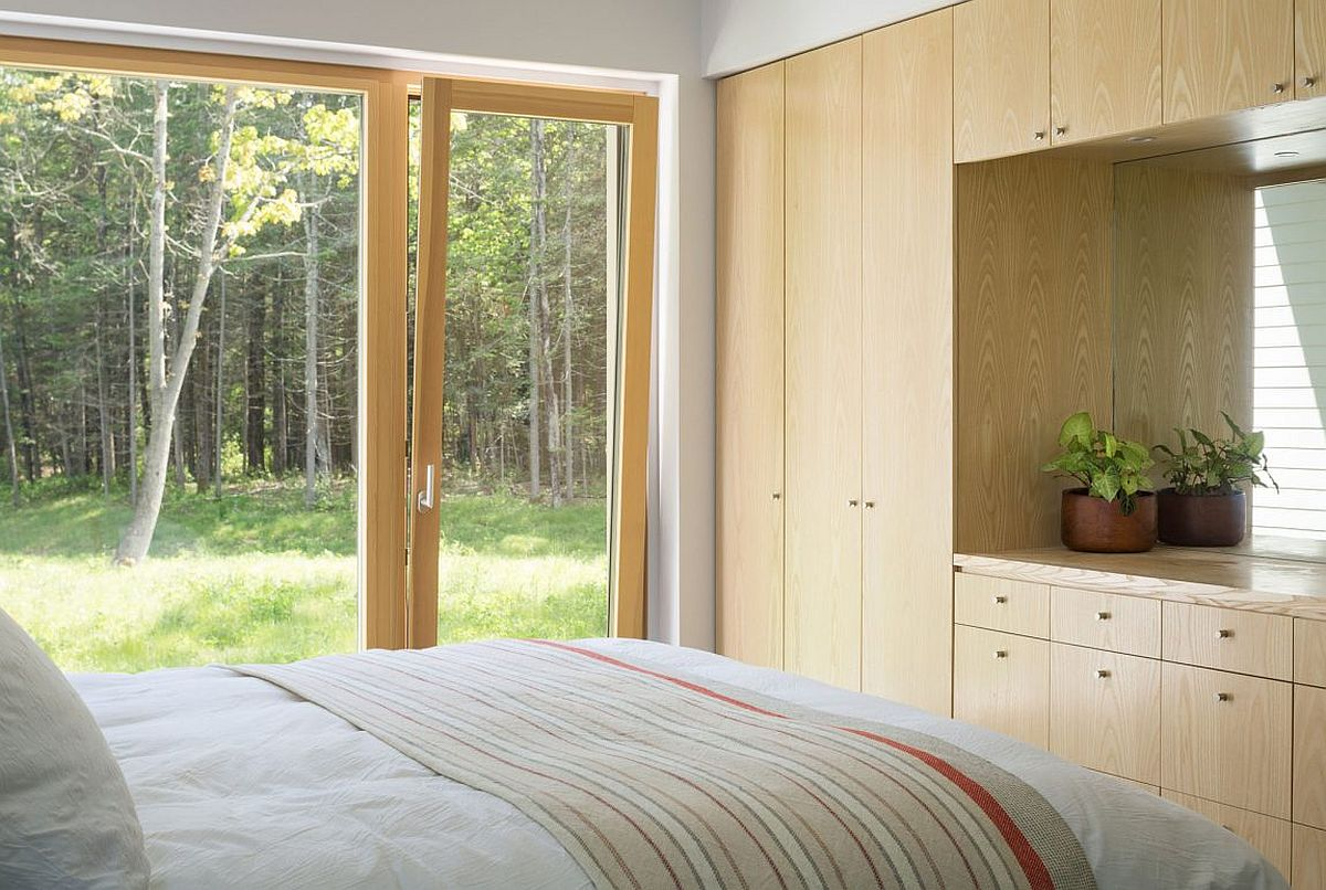 Large doors connect the bedroom with the pine forest and scenery outside