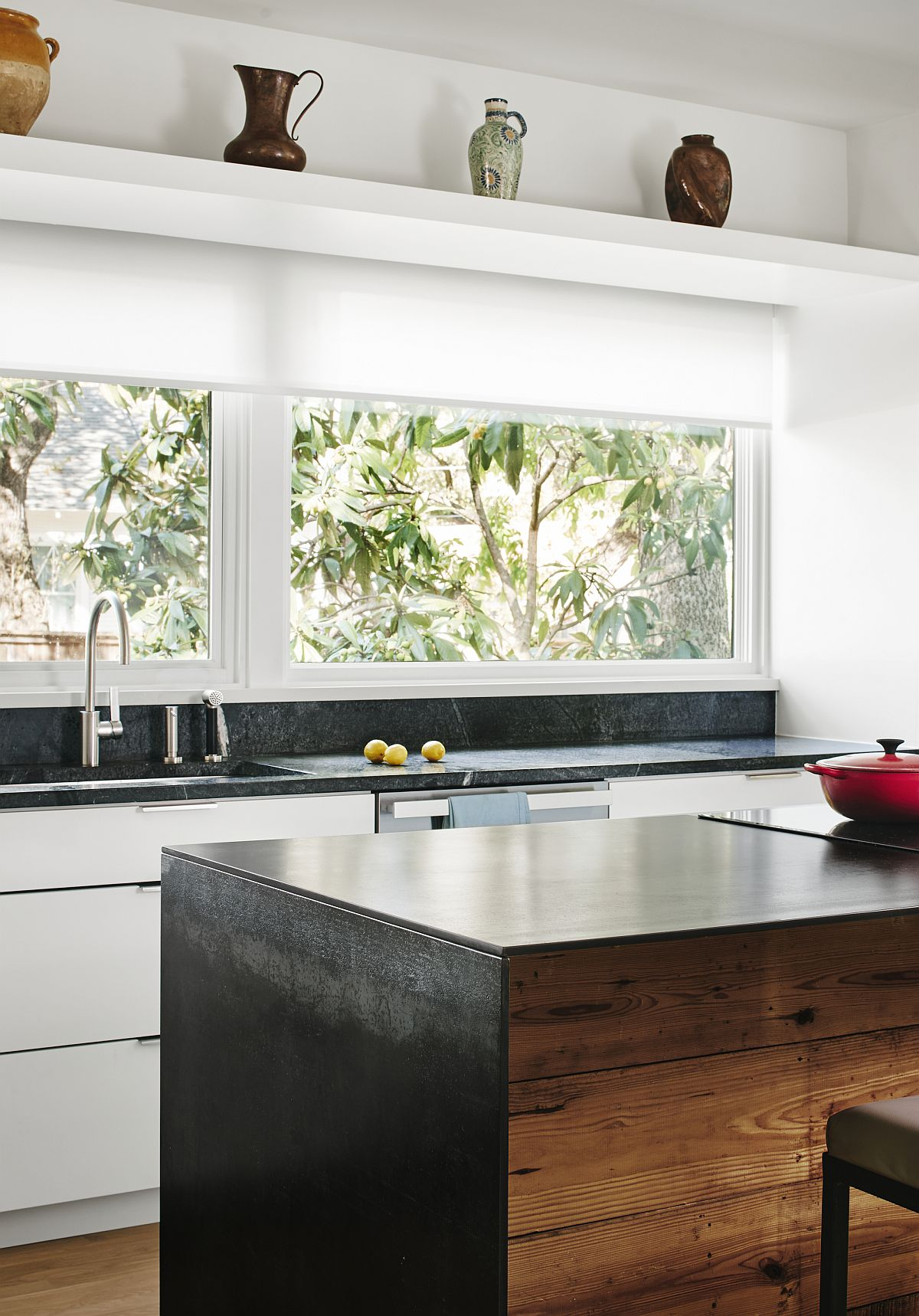 Large window connects the kitchen with the green yard outside