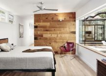 Master bedroom with accent wooden wall opens up towards the outdoors