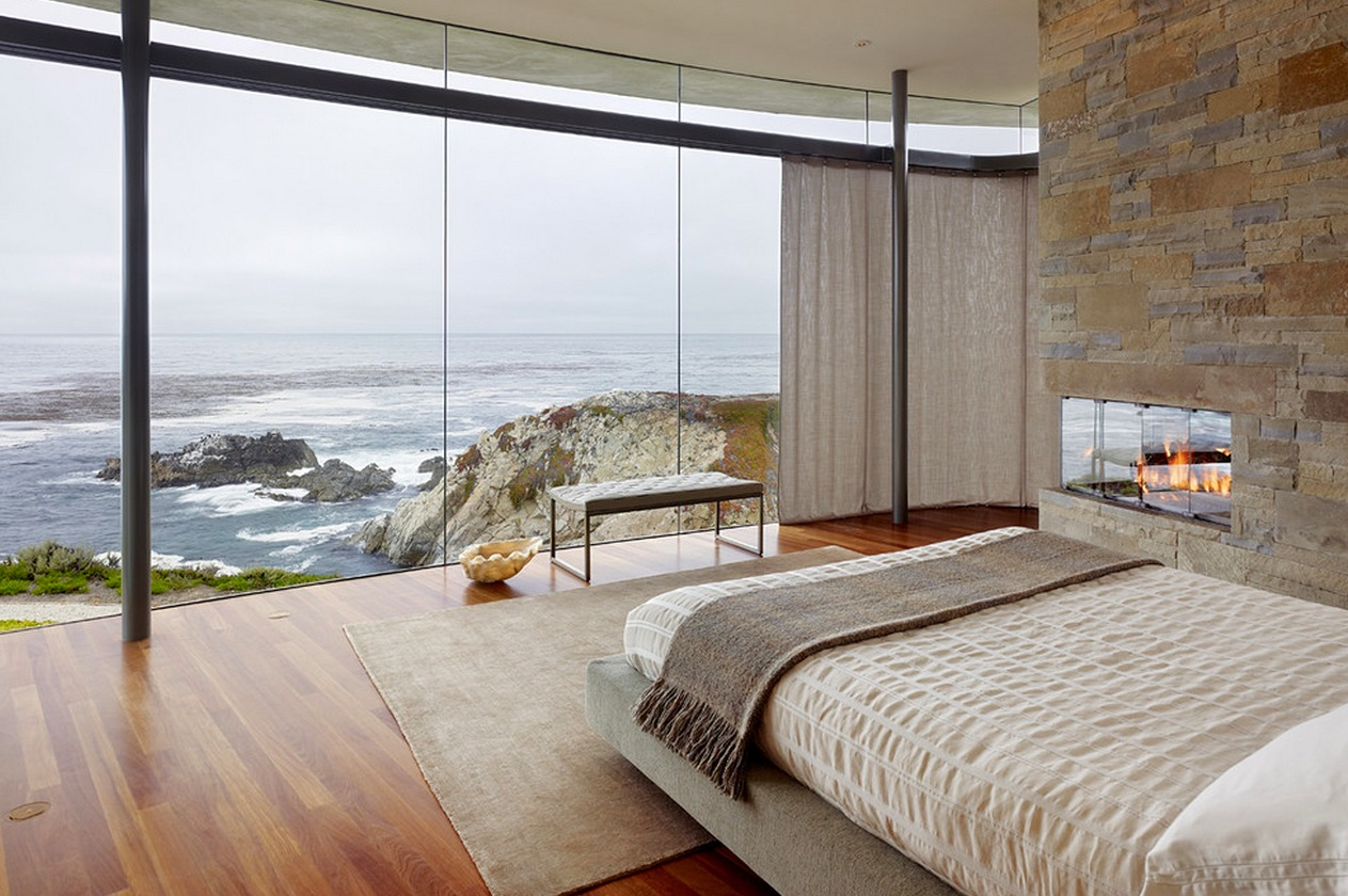 View in gallery Modern bedroom with a bench and an ocean view