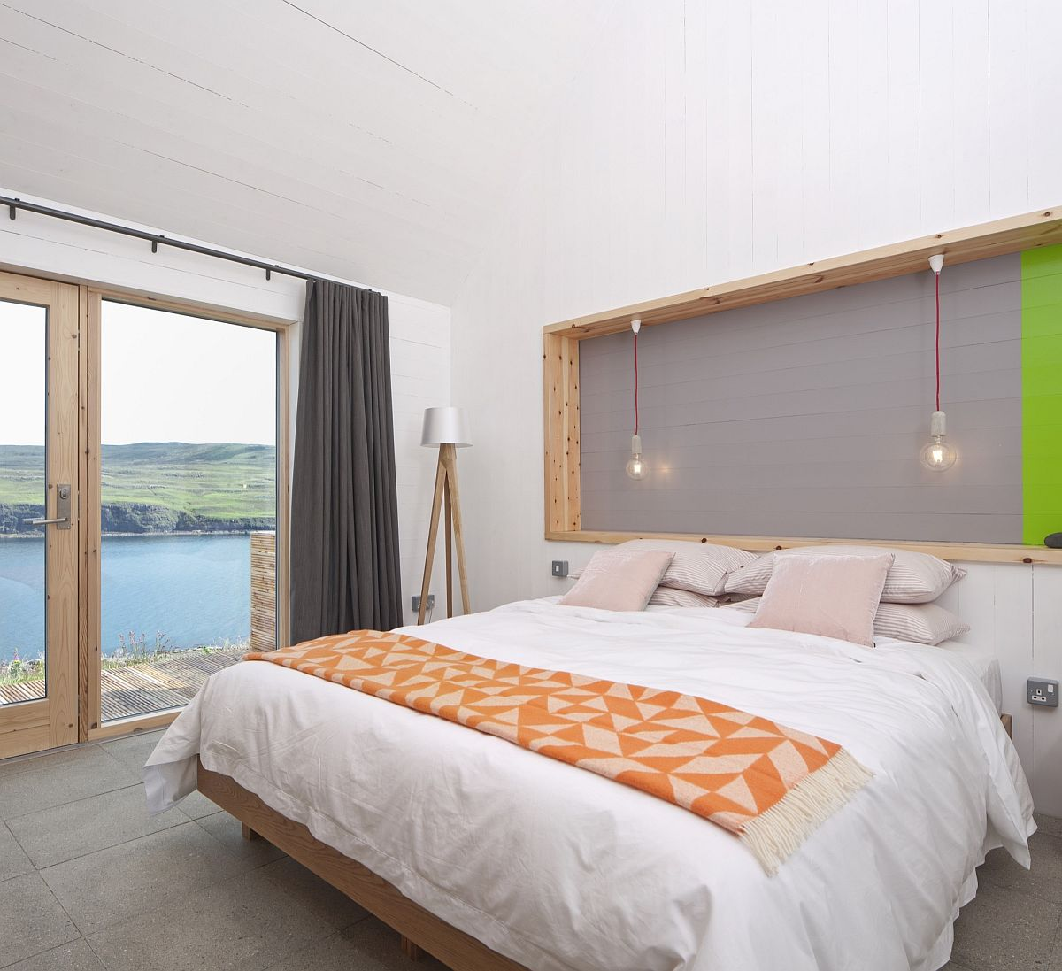 Modern bedroom with nature views and pops of orange and green